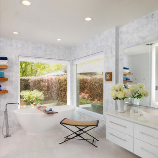 Example of a trendy beige floor bathroom design in New Orleans with flat-panel cabinets, white cabinets, gray walls, a vessel sink and white countertops