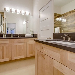 Bathroom - contemporary brown tile and ceramic tile porcelain floor and beige floor bathroom idea in San Diego with shaker cabinets, light wood cabinets, a two-piece toilet, beige walls, an undermount sink, solid surface countertops, a hinged shower door and brown countertops