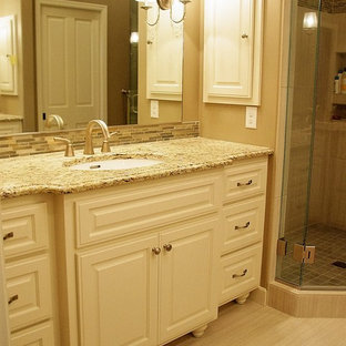 Large cottage chic master beige tile and ceramic tile ceramic floor corner shower photo in Minneapolis with an undermount sink, raised-panel cabinets, white cabinets, granite countertops and beige walls