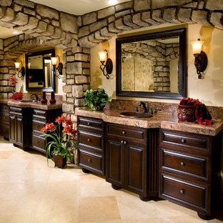Inspiration for a large mediterranean master travertine floor and beige floor bathroom remodel in Orange County with raised-panel cabinets, dark wood cabinets, beige walls, a drop-in sink and granite countertops