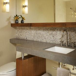 Idéer för ett mellanstort modernt badrum med dusch, med ett undermonterad handfat, kakel i småsten, beige väggar, klinkergolv i keramik, öppna hyllor, skåp i mellenmörkt trä, en toalettstol med separat cisternkåpa, grå kakel och beiget golv