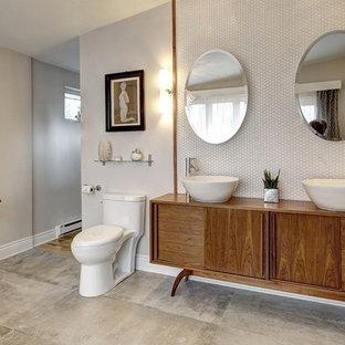 Diseño de cuarto de baño principal, vintage, grande, con armarios tipo mueble, puertas de armario de madera oscura, sanitario de una pieza, baldosas y/o azulejos blancos, baldosas y/o azulejos de cerámica, paredes grises, suelo de baldosas de cerámica, lavabo sobreencimera, encimera de madera, suelo gris y encimeras marrones