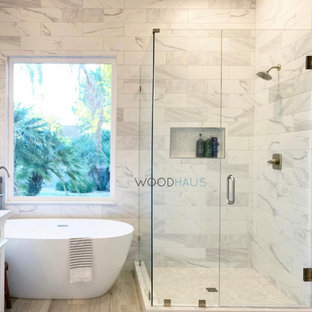 Mid-sized contemporary master bathroom in Miami with shaker cabinets, turquoise cabinets, a freestanding tub, a corner shower, a one-piece toilet, beige tile, ceramic tile, beige walls, wood-look tile, an undermount sink, quartzite benchtops, beige floor, a hinged shower door, white benchtops, a shower seat, a double vanity, a freestanding vanity, vaulted and panelled walls.