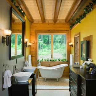 Diseño de cuarto de baño principal, rural, con lavabo sobreencimera, armarios tipo mueble, puertas de armario de madera en tonos medios, bañera con patas y paredes amarillas