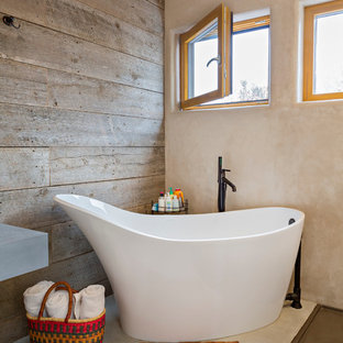 Mid-sized southwest master concrete floor and gray floor freestanding bathtub photo in Denver with brown walls, an undermount sink, concrete countertops and gray countertops