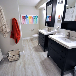 Bathroom - mid-sized transitional white tile and ceramic tile light wood floor bathroom idea in Calgary with an integrated sink, flat-panel cabinets, dark wood cabinets, solid surface countertops, a two-piece toilet and gray walls