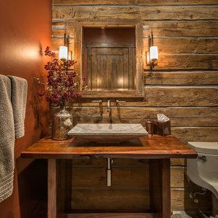 Foto de cuarto de baño con ducha, rústico, grande, con lavabo sobreencimera, armarios abiertos, puertas de armario de madera oscura, encimera de madera, sanitario de una pieza, parades naranjas y suelo de pizarra