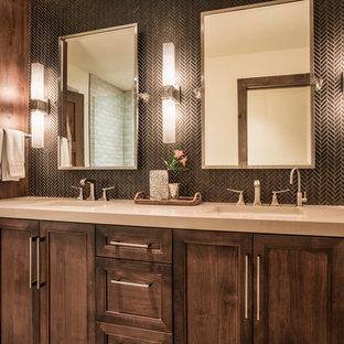 Foto de cuarto de baño rústico, de tamaño medio, con lavabo bajoencimera, armarios con paneles empotrados, puertas de armario de madera en tonos medios, encimera de acrílico, baldosas y/o azulejos negros, baldosas y/o azulejos en mosaico, paredes beige, ducha esquinera y ducha con puerta con bisagras