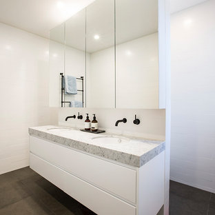 This is an example of a contemporary bathroom in Melbourne with flat-panel cabinets, white cabinets, an open shower, white walls, an undermount sink and grey floor.