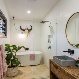 Inspiration for a beach style master wet room bathroom in Gold Coast - Tweed with flat-panel cabinets, medium wood cabinets, a freestanding tub, white walls, a vessel sink, wood benchtops, beige floor, an open shower and brown benchtops.