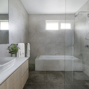 Modern wet room bathroom in Melbourne with flat-panel cabinets, light wood cabinets, a drop-in tub, gray tile, a vessel sink, grey floor, white benchtops, a single vanity and a floating vanity.