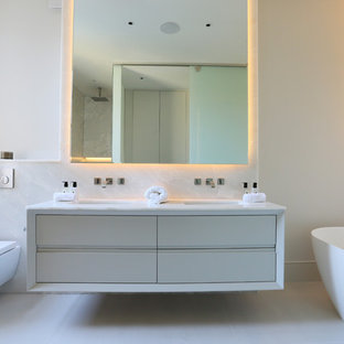 Inspiration for a medium sized modern bathroom in London with flat-panel cabinets, beige cabinets, a freestanding bath, a wall mounted toilet, white tiles, a wall-mounted sink, white floors, white worktops and white walls.