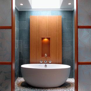 ボストンの中くらいのコンテンポラリースタイルのおしゃれなマスターバスルーム (アンダーカウンター洗面器、フラットパネル扉のキャビネット、中間色木目調キャビネット、珪岩の洗面台、置き型浴槽、緑のタイル、石タイル、緑の壁、玉石タイル) の写真
