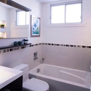 Immagine di una piccola stanza da bagno con doccia tradizionale con lavabo a consolle, ante lisce, ante grigie, top in superficie solida, WC monopezzo, piastrelle grigie, piastrelle in gres porcellanato, pareti bianche e pavimento in gres porcellanato