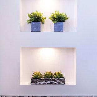 Idee per una piccola stanza da bagno con doccia tradizionale con lavabo a consolle, ante lisce, ante grigie, top in superficie solida, WC monopezzo, piastrelle grigie, piastrelle in gres porcellanato, pareti bianche e pavimento in gres porcellanato