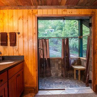 Diseño de cuarto de baño principal, rústico, de tamaño medio, con lavabo bajoencimera, armarios con paneles lisos, puertas de armario de madera oscura, ducha abierta, baldosas y/o azulejos blancos, baldosas y/o azulejos de piedra, paredes marrones y suelo de pizarra