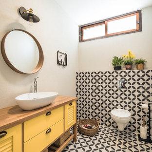 テルアビブの北欧スタイルのおしゃれなバスルーム (浴槽なし) (ルーバー扉のキャビネット、黄色いキャビネット、モノトーンのタイル、白い壁、ベッセル式洗面器、木製洗面台、マルチカラーの床、ブラウンの洗面カウンター、洗面台1つ、独立型洗面台) の写真
