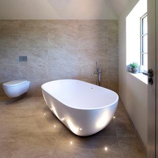 ウエストミッドランズの大きいコンテンポラリースタイルのおしゃれなマスターバスルーム (フラットパネル扉のキャビネット、淡色木目調キャビネット、置き型浴槽、オープン型シャワー、壁掛け式トイレ、ベージュのタイル、セラミックタイル、白い壁、セラミックタイルの床) の写真