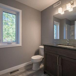 Diseño de cuarto de baño con ducha, de estilo americano, de tamaño medio, con armarios estilo shaker, puertas de armario marrones, bañera empotrada, ducha empotrada, sanitario de dos piezas, baldosas y/o azulejos grises, baldosas y/o azulejos de vidrio, paredes grises, suelo laminado, lavabo bajoencimera, encimera de cuarcita, suelo gris y ducha con cortina