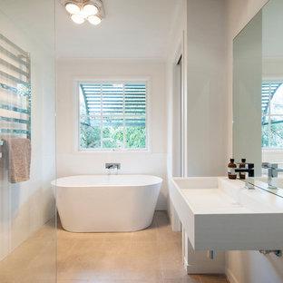 Idéer för att renovera ett mellanstort funkis badrum med dusch, med ett väggmonterat handfat, bänkskiva i akrylsten, ett fristående badkar, vit kakel och vita väggar