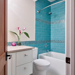 Diseño de cuarto de baño minimalista con lavabo bajoencimera, armarios con paneles lisos, puertas de armario blancas, encimera de piedra caliza, combinación de ducha y bañera, baldosas y/o azulejos azules, baldosas y/o azulejos de porcelana, paredes beige y suelo de baldosas de porcelana