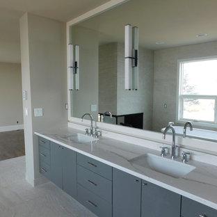 Imagen de cuarto de baño principal, minimalista, de tamaño medio, con armarios con paneles lisos, puertas de armario grises, baldosas y/o azulejos multicolor, baldosas y/o azulejos con efecto espejo, paredes grises, suelo de baldosas de cerámica, lavabo encastrado, encimera de granito y suelo gris
