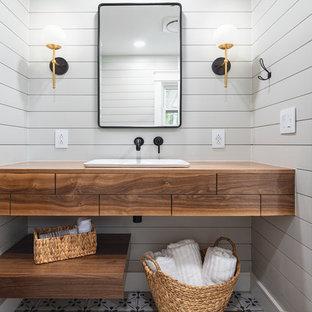Inspiration pour une salle de bain rustique de taille moyenne avec un placard en trompe-l'oeil, des portes de placard en bois brun, une baignoire en alcôve, un combiné douche/baignoire, un WC séparé, un carrelage blanc, des carreaux de céramique, un mur gris, un sol en carrelage de porcelaine, un plan de toilette en bois, un sol gris, une cabine de douche avec un rideau, une vasque, meuble-lavabo suspendu et du lambris de bois.