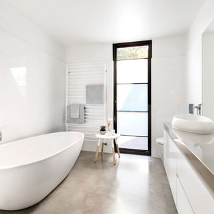 Photo of a large contemporary master bathroom in Melbourne with grey cabinets, a freestanding tub, a corner shower, a one-piece toilet, white tile, ceramic tile, yellow walls, concrete floors, a vessel sink, engineered quartz benchtops, a hinged shower door, grey benchtops, a single vanity and a floating vanity.