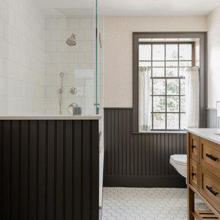 Cette photo montre une salle de bain chic de taille moyenne pour enfant avec un carrelage blanc, des carreaux de céramique, un sol en carrelage de céramique, un lavabo encastré, un plan de toilette en marbre, une cabine de douche à porte battante, un plan de toilette blanc, un placard à porte shaker, des portes de placard en bois brun, une douche d'angle, un mur beige, un sol blanc, meuble double vasque, meuble-lavabo sur pied et boiseries.