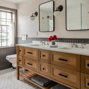 Идея дизайна: главная ванная комната среднего размера в стиле неоклассика (современная классика) с белой плиткой, керамической плиткой, полом из керамической плитки, врезной раковиной, белой столешницей, тумбой под две раковины, напольной тумбой, фасадами в стиле шейкер, фасадами цвета дерева среднего тона, душем в нише, инсталляцией, разноцветными стенами, белым полом, душем с распашными дверями, панелями на части стены и обоями на стенах