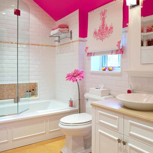 This is an example of a traditional kids bathroom in Montreal with a vessel sink, recessed-panel cabinets, white cabinets, an alcove tub, a shower/bathtub combo, a two-piece toilet, white tile, subway tile, pink walls and yellow floor.