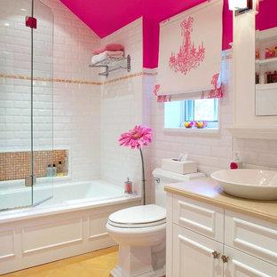 На фото: детские ванные комнаты в классическом стиле с настольной раковиной, фасадами с утопленной филенкой, белыми фасадами, ванной в нише, душем над ванной, раздельным унитазом, белой плиткой, плиткой кабанчик, розовыми стенами и желтым полом