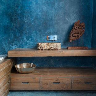 Foto de cuarto de baño de estilo zen con armarios abiertos, puertas de armario de madera oscura, bañera encastrada, paredes azules, encimera de madera y encimeras marrones