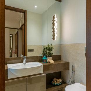 Immagine di una piccola stanza da bagno con doccia design con ante lisce, ante marroni, WC sospeso, piastrelle beige, pareti bianche, lavabo da incasso, pavimento beige e top marrone