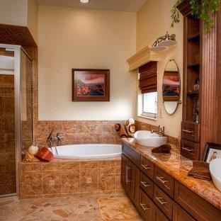 Réalisation d'une salle de bain principale design de taille moyenne avec un placard à porte shaker, des portes de placard en bois sombre, une baignoire posée, une douche d'angle, un mur beige, un sol en galet, une vasque, un plan de toilette en onyx, un sol beige et une cabine de douche à porte battante.