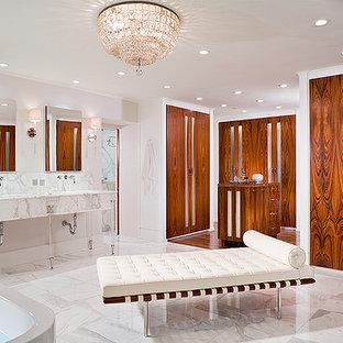 ニューヨークの大きいトランジショナルスタイルのおしゃれなマスターバスルーム (家具調キャビネット、白いキャビネット、置き型浴槽、洗い場付きシャワー、分離型トイレ、白いタイル、大理石タイル、白い壁、大理石の床、アンダーカウンター洗面器、大理石の洗面台、白い床、オープンシャワー、白い洗面カウンター) の写真