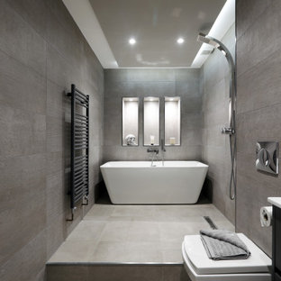 This is an example of a large contemporary bathroom in Sussex with flat-panel cabinets, black cabinets, a freestanding bath, a wall mounted toilet, grey tiles, an integrated sink, grey floors, an open shower, white worktops and a wall niche.