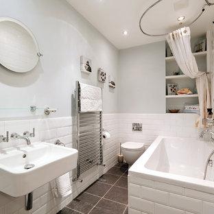 Immagine di una piccola stanza da bagno per bambini nordica con nessun'anta, vasca da incasso, WC sospeso, piastrelle bianche, piastrelle diamantate, lavabo sospeso, vasca/doccia, pavimento con piastrelle in ceramica, ante bianche, pareti blu e doccia con tenda