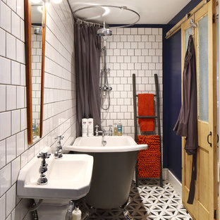 Design ideas for a small scandinavian family bathroom in Sussex with a freestanding bath, a shower/bath combination, a one-piece toilet, white tiles, metro tiles, blue walls, ceramic flooring and a pedestal sink.