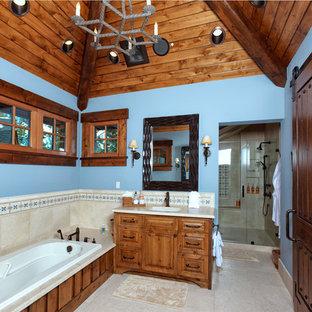 サクラメントの大きいラスティックスタイルのおしゃれなバスルーム (浴槽なし) (レイズドパネル扉のキャビネット、中間色木目調キャビネット、ドロップイン型浴槽、ベージュのタイル、セラミックタイル、青い壁、セラミックタイルの床、アンダーカウンター洗面器、ベージュの床、アルコーブ型シャワー、開き戸のシャワー) の写真