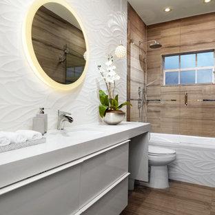 На фото: маленькая ванная комната в современном стиле с плоскими фасадами, белыми фасадами, угловой ванной, белой плиткой, плиткой из листового стекла, душевой кабиной, столешницей из искусственного камня, душем с распашными дверями, белой столешницей, тумбой под одну раковину и встроенной тумбой с