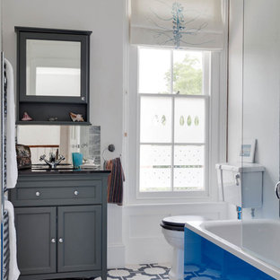 Classic bathroom in Kent with recessed-panel cabinets, grey cabinets, a two-piece toilet, white walls and blue floors.