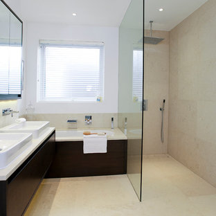 Photo of a medium sized contemporary ensuite bathroom in Dorset with a vessel sink, flat-panel cabinets, dark wood cabinets, a submerged bath, a corner shower, beige tiles, white walls and beige floors.