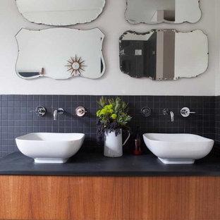 Idées déco pour une salle de bain contemporaine avec une vasque, un placard sans porte, des portes de placard en bois brun, un carrelage noir et un plan de toilette noir.