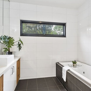 This is an example of a contemporary bathroom in Geelong with flat-panel cabinets, medium wood cabinets, a drop-in tub, white tile, a vessel sink, grey floor and white benchtops.
