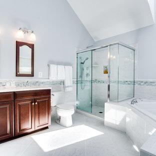 Inredning av ett modernt mellanstort en-suite badrum, med luckor med upphöjd panel, skåp i mörkt trä, ett hörnbadkar, en hörndusch, ett urinoar, grå kakel, keramikplattor, grå väggar, klinkergolv i keramik, ett undermonterad handfat och granitbänkskiva