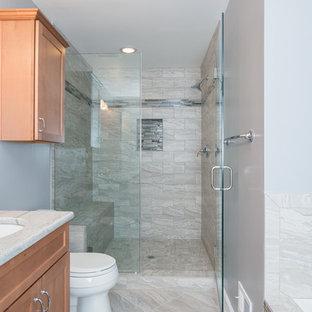 Imagen de cuarto de baño principal, tradicional, de tamaño medio, con lavabo bajoencimera, armarios con paneles empotrados, puertas de armario de madera oscura, encimera de granito, bañera encastrada, ducha empotrada, sanitario de dos piezas, baldosas y/o azulejos beige, baldosas y/o azulejos de porcelana, paredes azules, suelo de baldosas de porcelana, suelo gris y ducha con puerta con bisagras