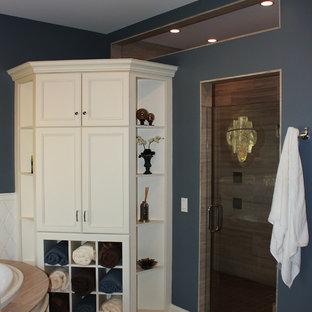 Esempio di una grande stanza da bagno padronale chic con ante con riquadro incassato, ante bianche, vasca ad angolo, lastra di pietra, pareti blu, pavimento in bambù, lavabo sottopiano e top in superficie solida