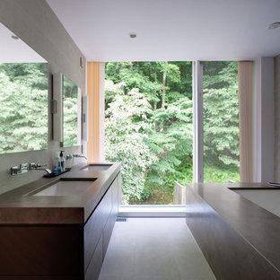 Foto di una stanza da bagno moderna con lavabo sottopiano, ante in legno bruno, vasca sottopiano, piastrelle grigie, top in cemento, piastrelle di cemento e ante lisce