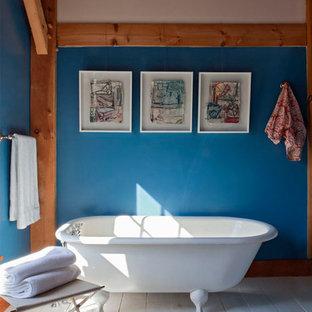 Modelo de cuarto de baño principal, romántico, con bañera con patas, baldosas y/o azulejos azules, suelo de madera clara y suelo gris
